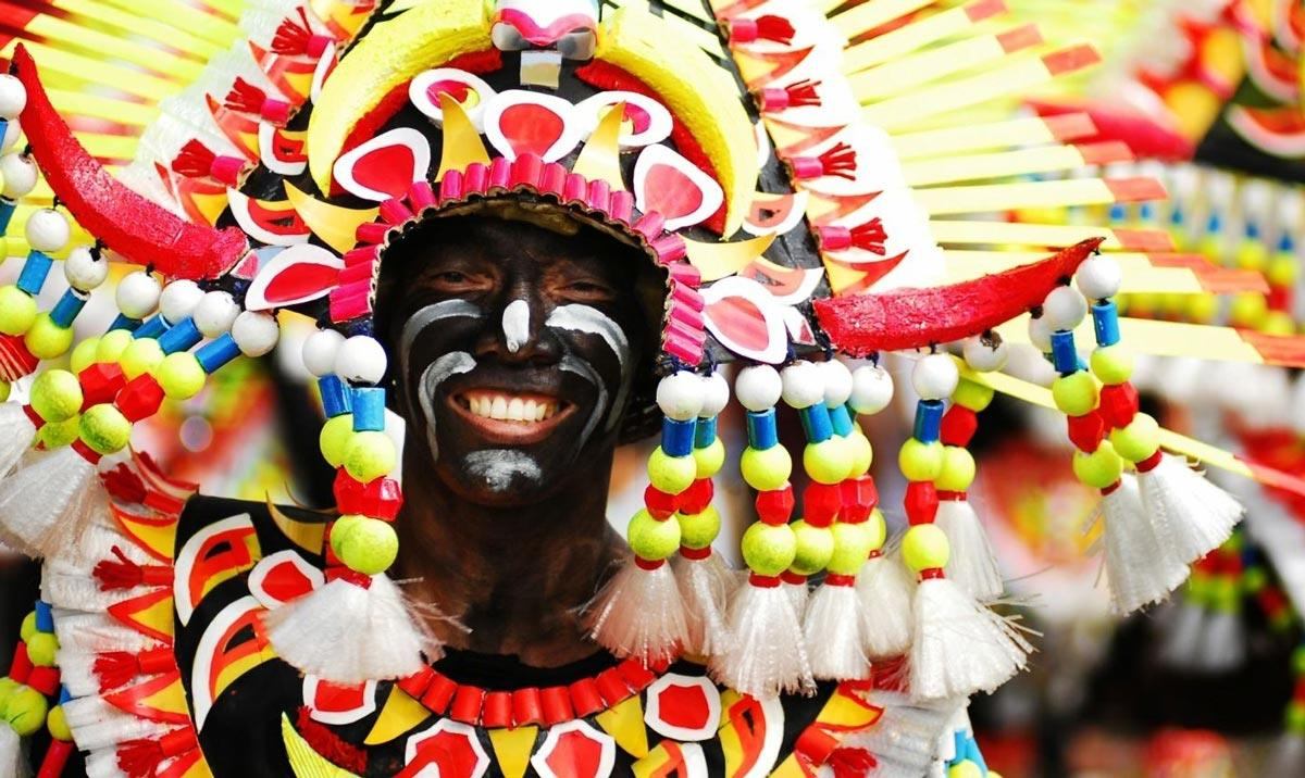 Người diễu hành sơn mặt bằng bồ hóng và mặc trang phục dân tộc rực rỡ